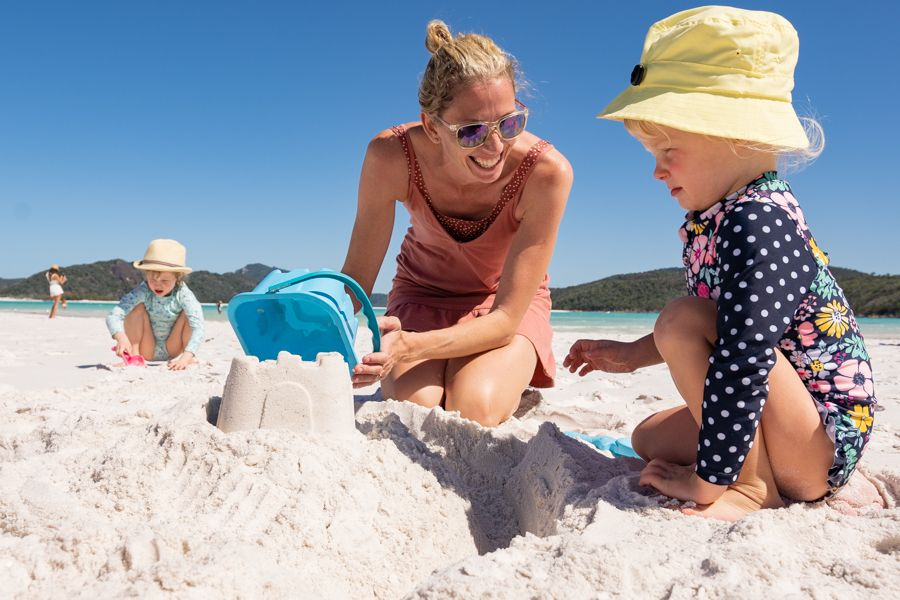 Mother and Daughter making a sand castle at Whitehaven Beach, Whitsundays, Australia