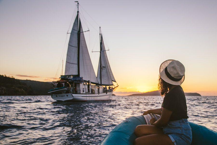 Girl looking a vessel at sunset, Whitsundays, Australia