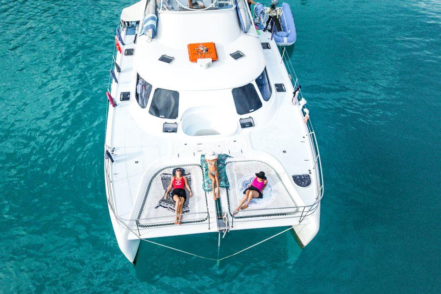 Three girls sunbathing in a boat, Whitsundays, Australia