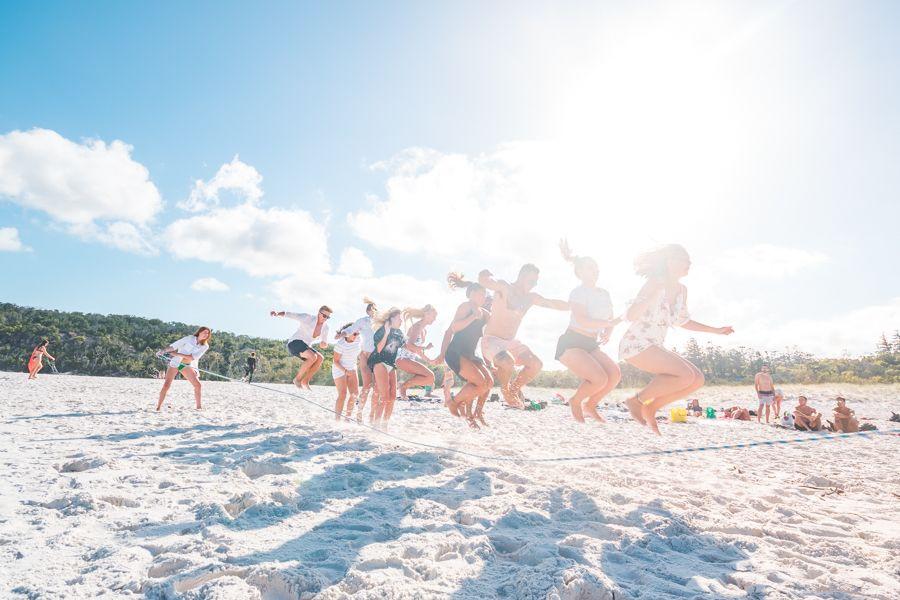Friends jumping in Whitehaven Beach, Whitsundays, Australia