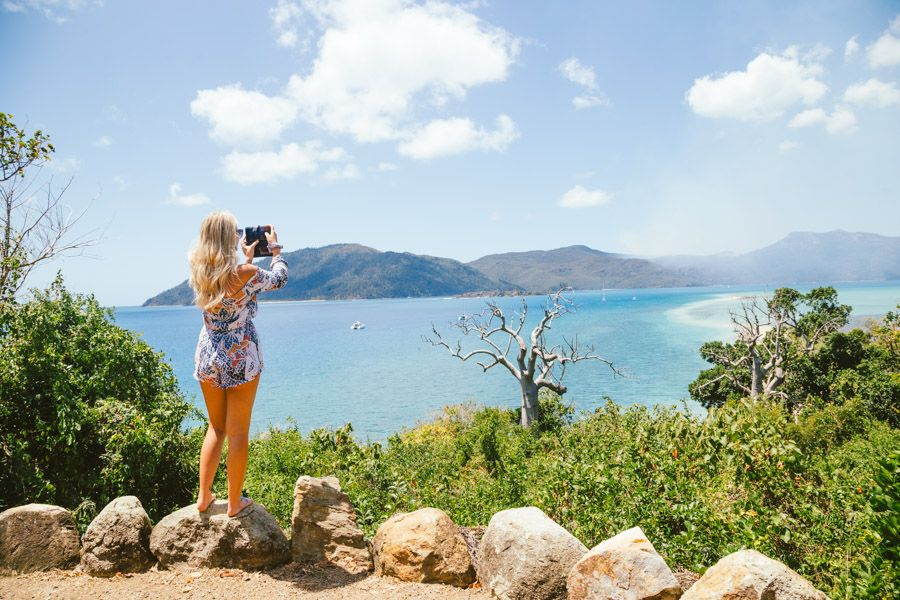 Girl taking a photograph at Langford Island Lookout, Whitsundays, Australia